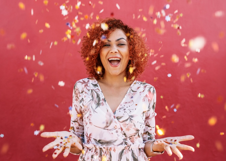 A happy woman with hands open, raining confetti