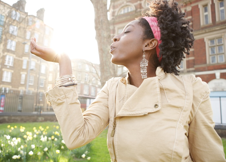 Young black woman holding the sun in her hand