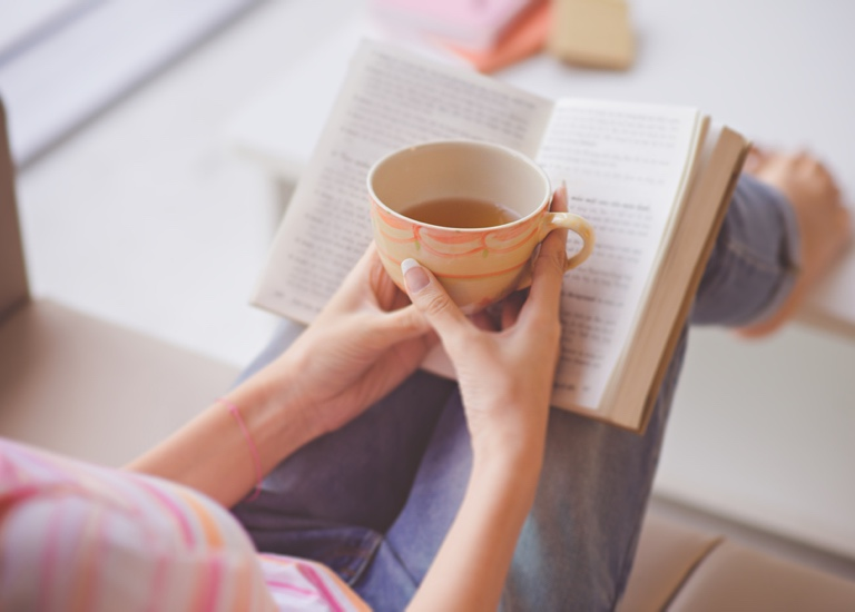 A woman reading a book quietly holding a cup of tea