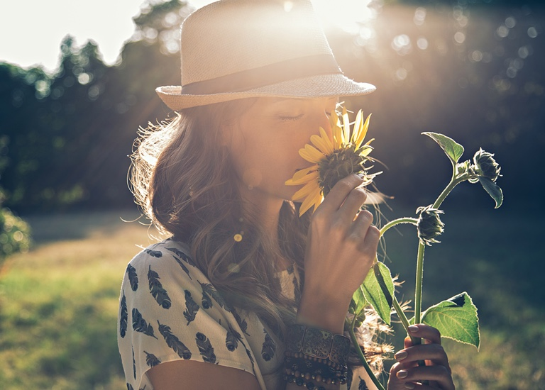 A woman smelling a sunflower