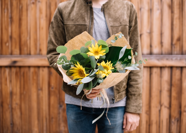 Man holding a bunch of flowers