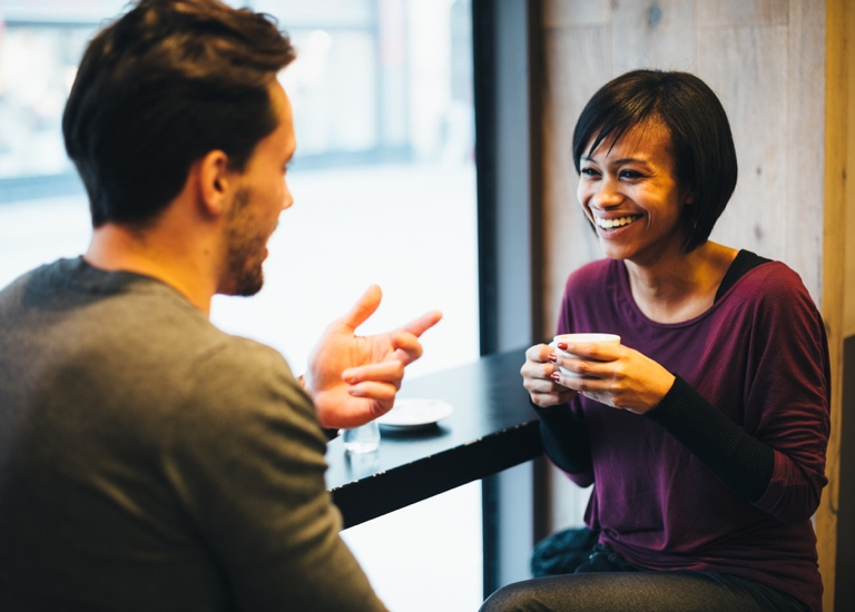 A man and a woman meet for coffee
